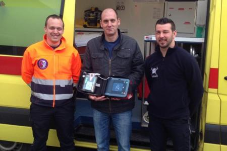 Thierry entouré de Nicolas et Logan avec le défibrillateur qui lui a sauvé la vie.